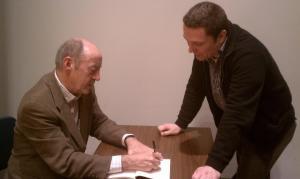 Billy Collins signs his poem for me, right befoe I crack him up.