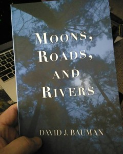 Cover image of poetry chapbook Moons, Roads, and Rivers by David J. Bauman. Dark trees, midnight blue and moonlight white lettering serif font