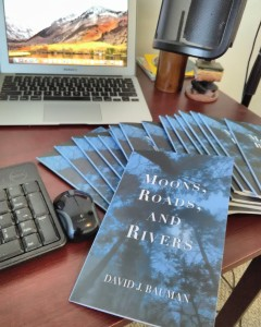 Poetry Chapbook Moons, Roads, and Rivers by David J. Bauman. Cover, midnight blue looking up through trees with moonlight. books, desk, mac, laptop, micraphone
